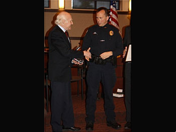 Sen. Herb Kohl presents an award to Onalaska police officer James Page.